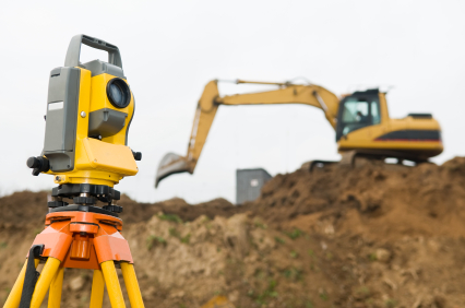 Surveyor equipment in front of working construction machinery loader