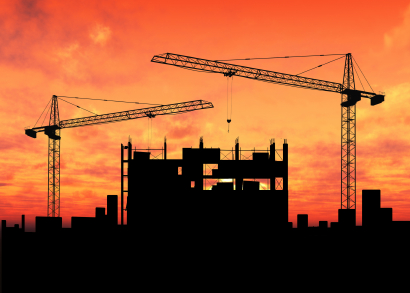 Construction of tall building with 2 cranes at sunset