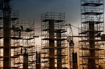 Construction of 3 tall buildings with a crane at dusk