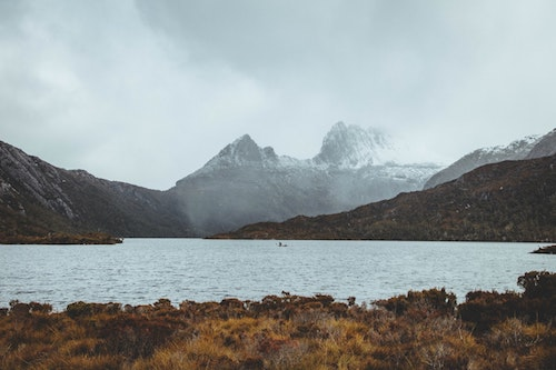Lake in front of Cradle Mountain covered in snow and fog